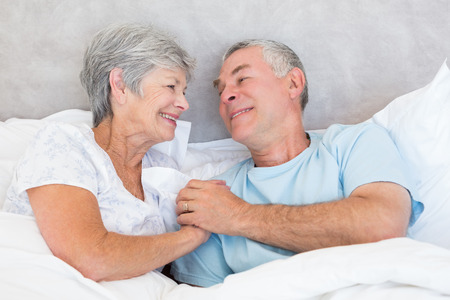 Romantic senior couple holding hands in bed at home photo