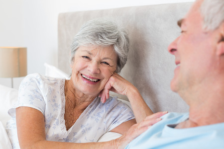 Portrait of happy senior woman with man in bed at home photo