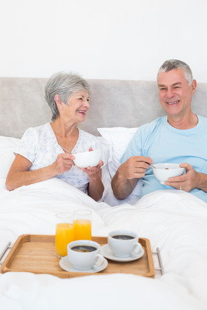 Happy senior couple having breakfast in bed at home photo