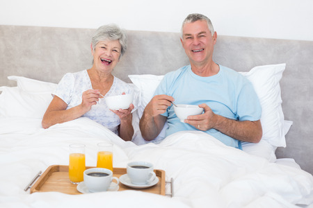 Portrait of happy senior couple having breakfast in bed at home photo