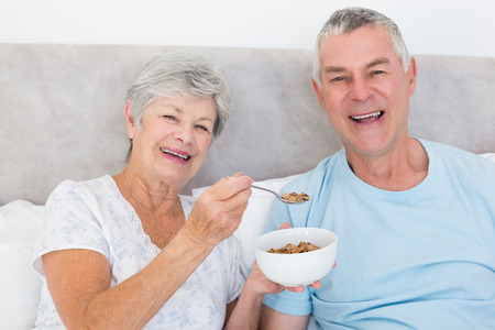 Portrait of happy senior woman feeding cereals to man in house photo