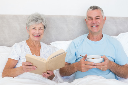 Portrait of happy senior couple with book and cereal bowl in bed at home photo