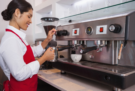 Pretty barista steaming jug of milk at coffee machine in a cafe photo