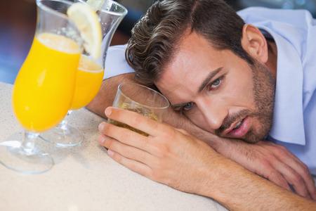slumped: Drunk businessman slumped on bar beside cocktail at the local bar