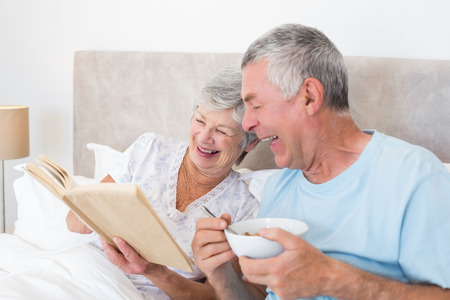 Happy senior couple reading book in bed at home photo