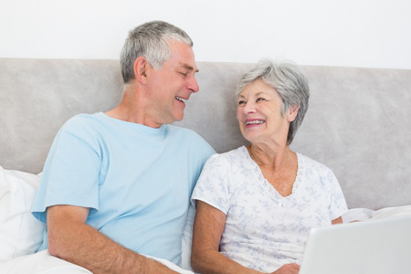 Happy senior couple with laptop looking at each other in bed at home photo