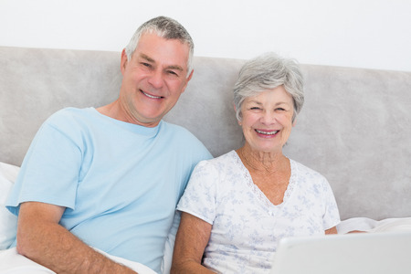Portrait of senior couple with laptop sitting in bed at home photo