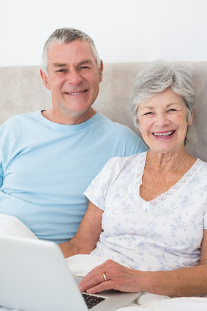 Portrait of happy senior couple with laptop in bed at home photo