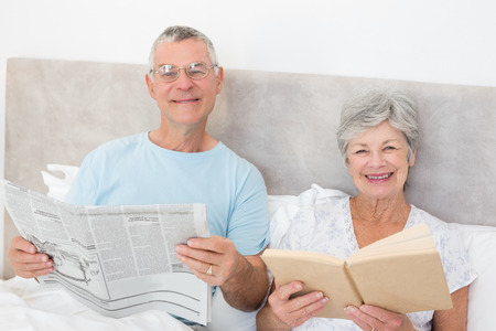 Portrait of senior couple holding newspaper and book in bed at home photo