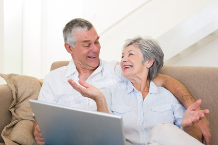 Loving senior couple with laptop looking at each other on sofa at home photo