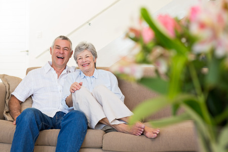 Portrait of happy senior couple relaxing on sofa at home photo