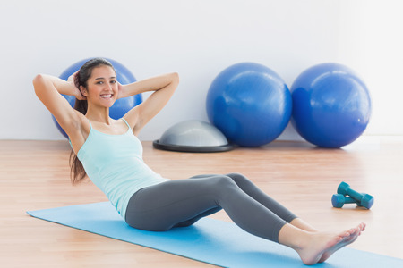 sit ups: Full length of a smiling young woman doing sit ups in fitness studio