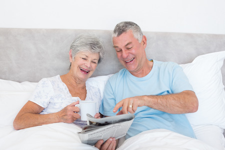 Happy senior couple reading newspaper together in bed at home photo