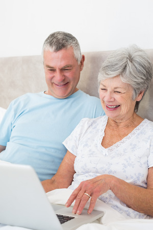 Senior couple using laptop computer while smiling in bed at home photo