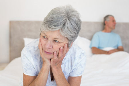 Sad senior woman looking away with man in background on bed at home photo
