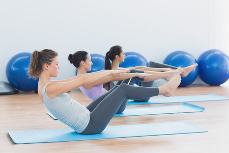 Side view of class stretching on mats at yoga class in fitness studio photo