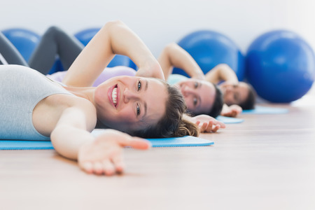 Side view portrait of fit class exercising in row at fitness studio Stock Photo