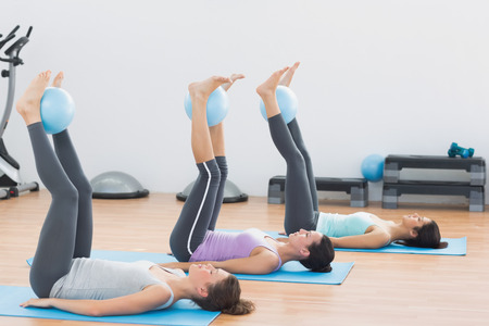 Side view of sporty young women holding balls between ankles in fitness studio photo