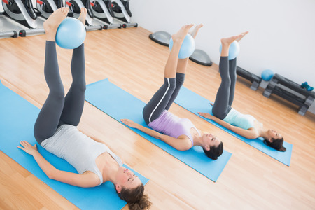 Full length of sporty young women holding balls between ankles in fitness studio photo