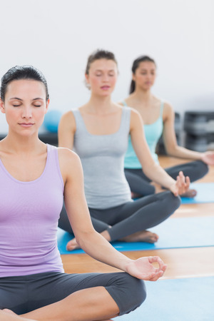 Sporty young women in lotus posture with eyes closed at a fitness studio photo