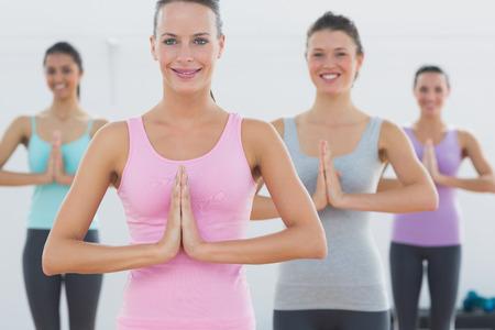 manos unidas: Mujeres deportivas jovenes hermosas con las manos juntas en el estudio de fitness Foto de archivo
