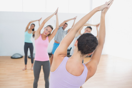 manos unidas: Clase deportiva y el instructor con las manos juntas en el gimnasio