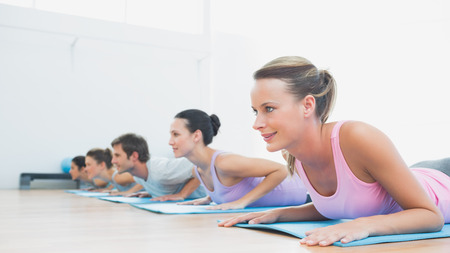 Side view of a fit class exercising in row at fitness studio photo