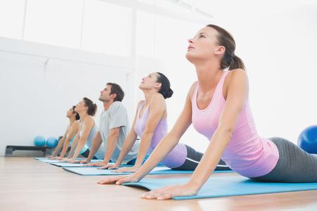 Zijaanzicht van een fit klasse oefenen in rij bij fitness-studio