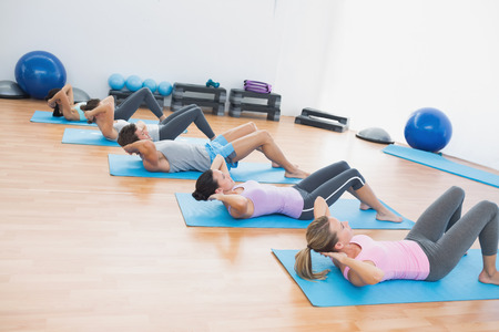 Full length side view of determined young people doing sit ups in fitness studio photo