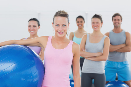 Portrait of an instructor holding exercise ball with fitness class in background at fitness studio photo