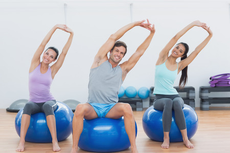 Portrait of smiling young people sitting on exercise balls and stretching up hands in the gym