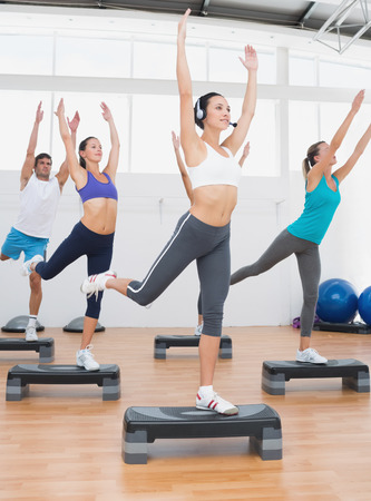 Female instructor with fitness class performing step aerobics exercise in gym photo