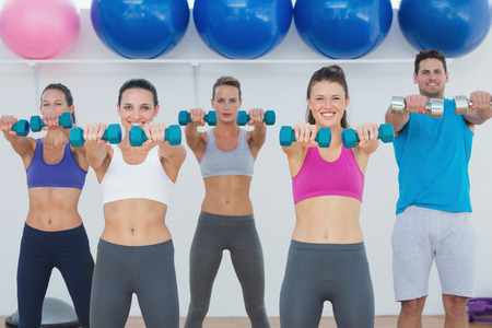 Portrait of fitness class and instructor exercising with dumbbells in the gym photo