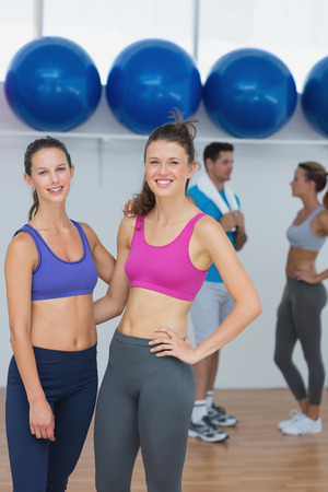Portrait of fit young women in sports bra with a couple in background in fitness studio photo