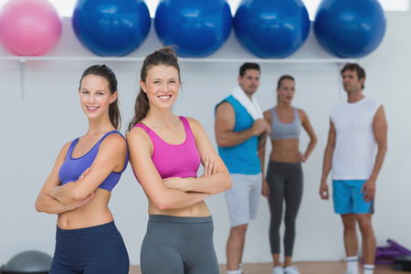 Portrait of fit young women in sports bra with friends in background in fitness studio photo
