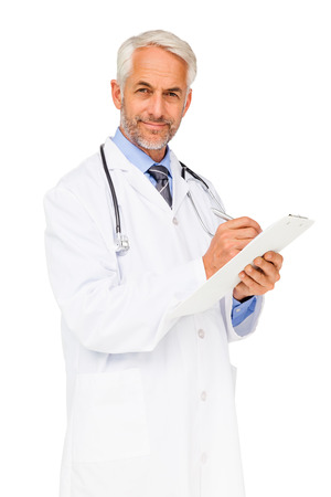 Portrait of a confident male doctor writing reports over white background photo