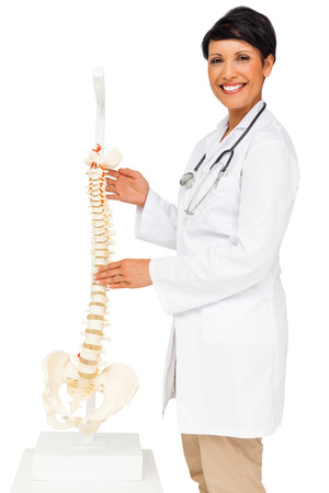 Side view portrait of a female doctor holding skeleton model over white background photo
