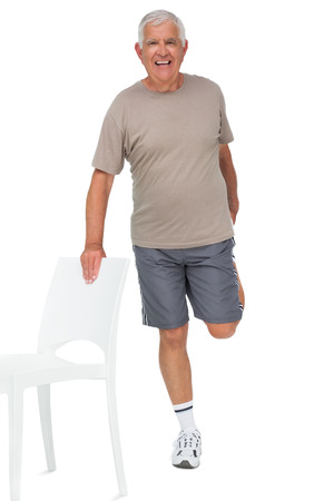 Full length portrait of a happy senior man stretching leg over white background