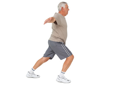 Full length side view of a senior man stretching hands over white background Stock Photo