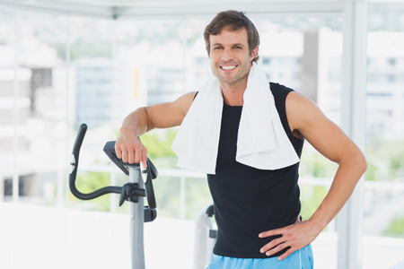 Portrait of a smiling young man standing at spinning class in a bright gym photo