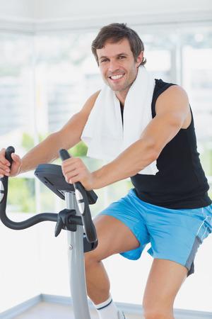 man working out: Retrato de un joven sonriente que se resuelve en la clase de spinning en un gimnasio brillante