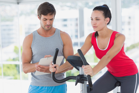 Fit woman with male instructor working out at spinning class in a bright gym photo