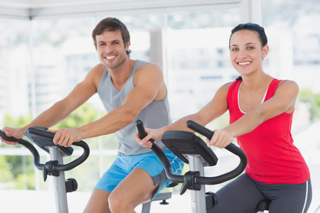 Smiling young couple working out at spinning class in a bright gym