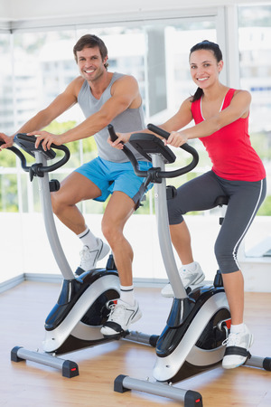 Smiling young couple working out at spinning class in a bright gym photo