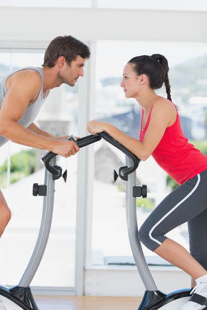 Determined young couple working out at spinning class in a bright gym photo