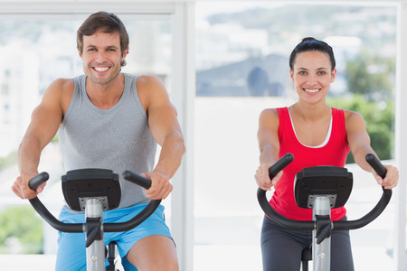 Smiling young couple working out at spinning class in a gym photo