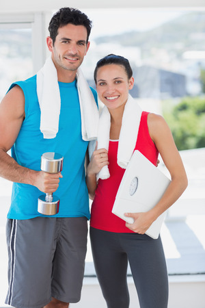 Portrait of a fit young couple standing with dumbbell and scale in a bright exercise room photo