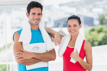 Portrait of a fit young couple standing in a bright exercise room photo