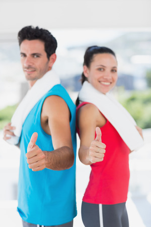 Portrait of a fit young couple gesturing thumbs up in a bright exercise room photo