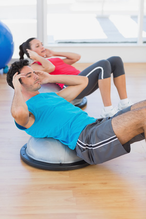 Young couple working out on dome balance in a bright gym photo